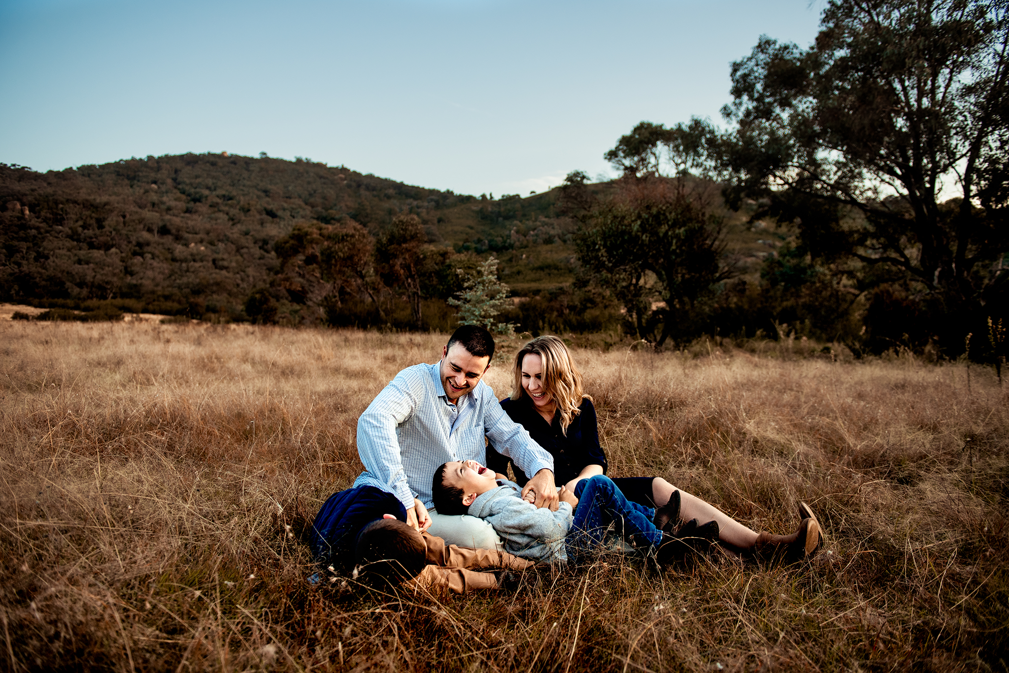 canberra family photographer family cuddling in the grass
